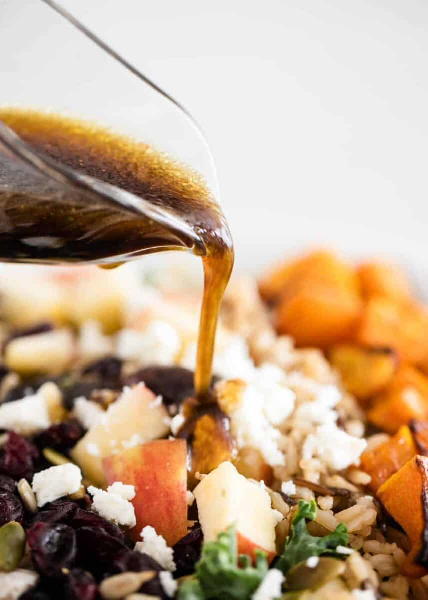pouring maple balsamic dressing on top of harvest salad