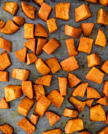 close up of roasted sweet potatoes on baking sheet