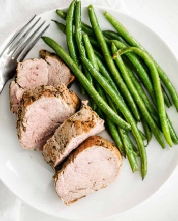 sliced pork tenderloin on a plate with green beans