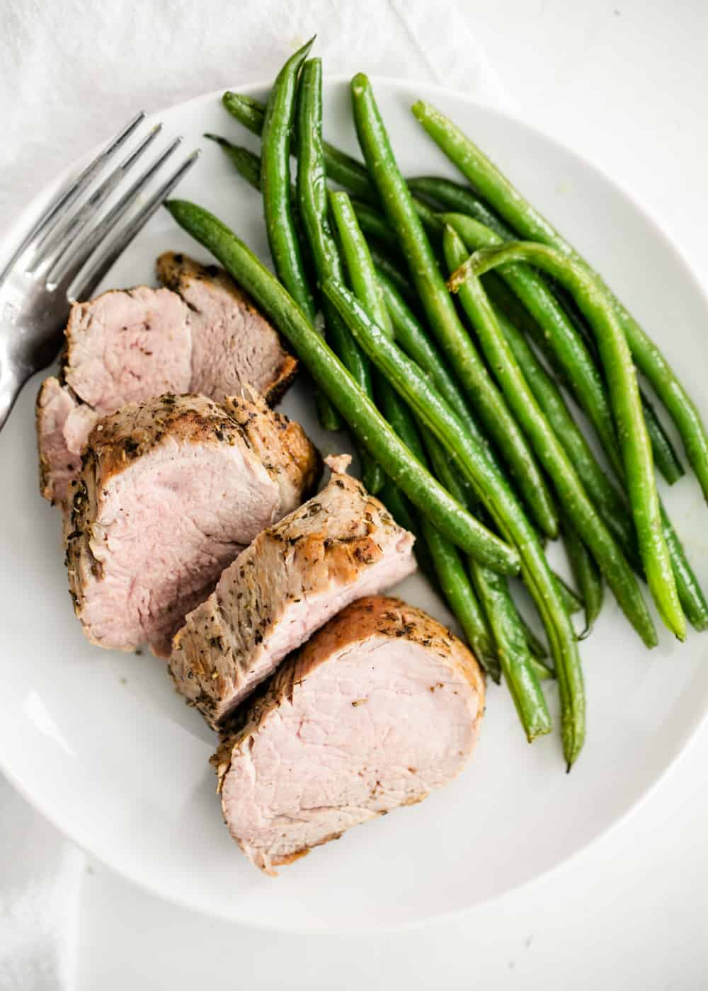 sliced pork tenderloin on a plate with green beans
