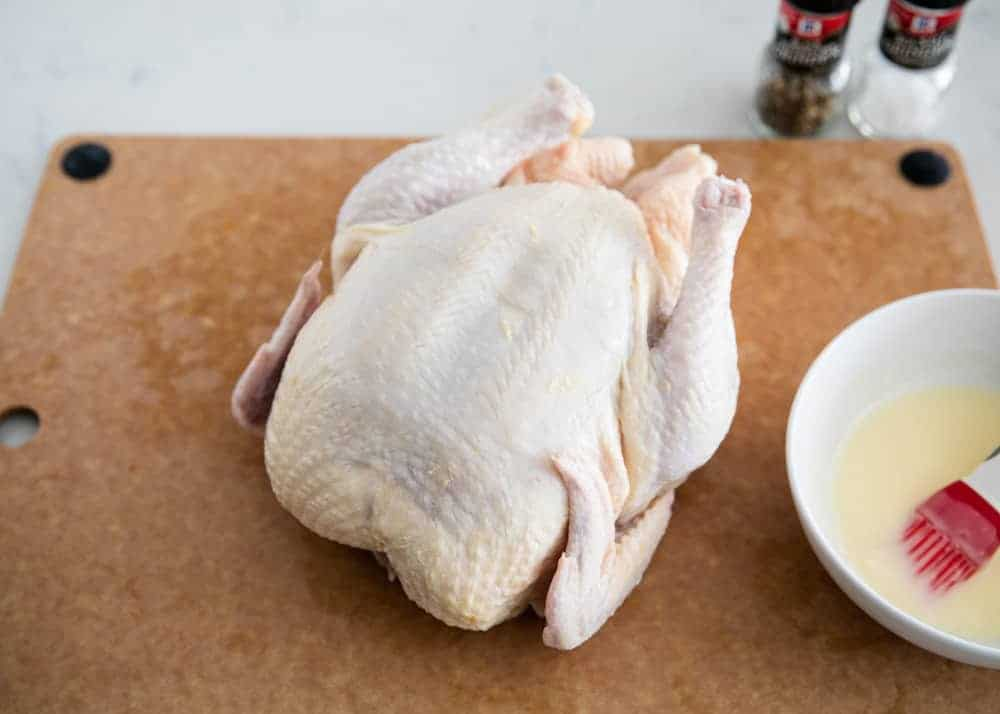 seasoning a raw whole chicken on a cutting board