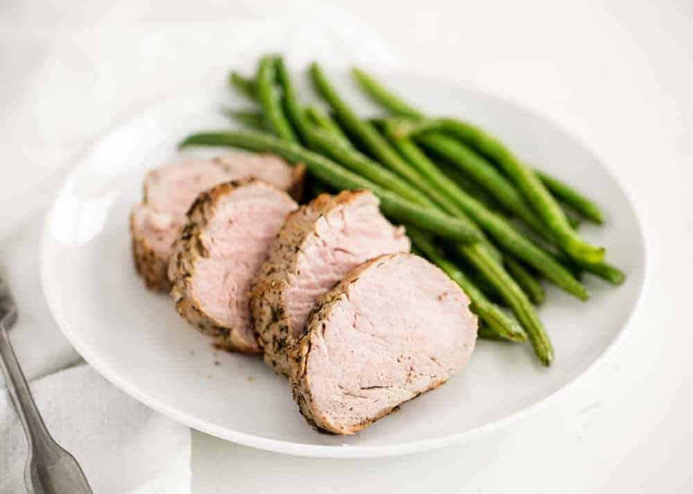 plate with sliced pork tenderloin and green beans