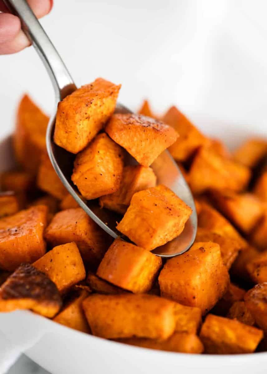 scooping up roasted sweet potatoes with a spoon