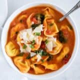 bowl of tomato tortellini soup with shaved parmesan on top
