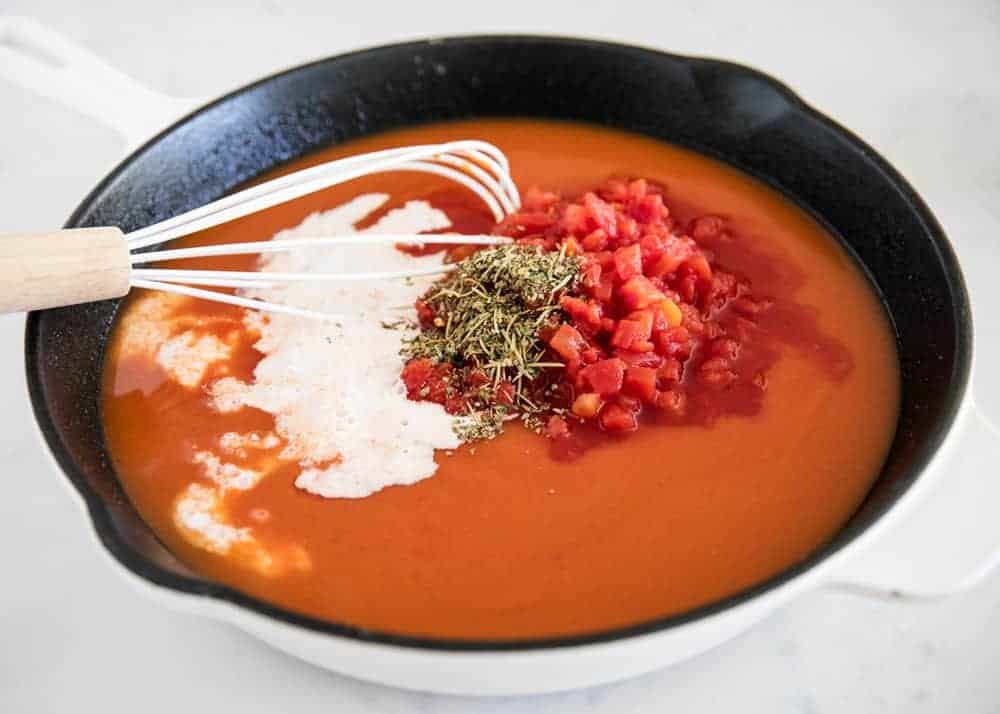 whisking together ingredients in skillet for tomato tortellini soup
