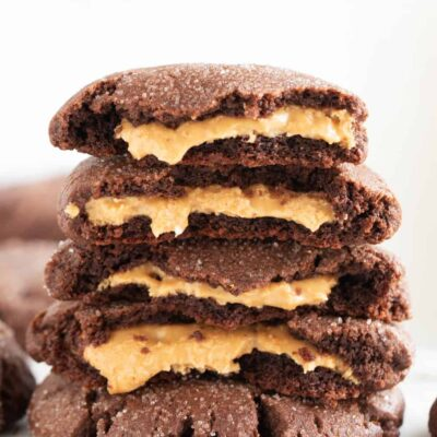 stack of chocolate peanut butter stuffed cookies with peanut butter filling oozing out