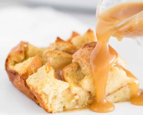 pouring caramel sauce over a slice of bread pudding