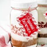 layered ingredients for peppermint brownies in a mason jar with a tag