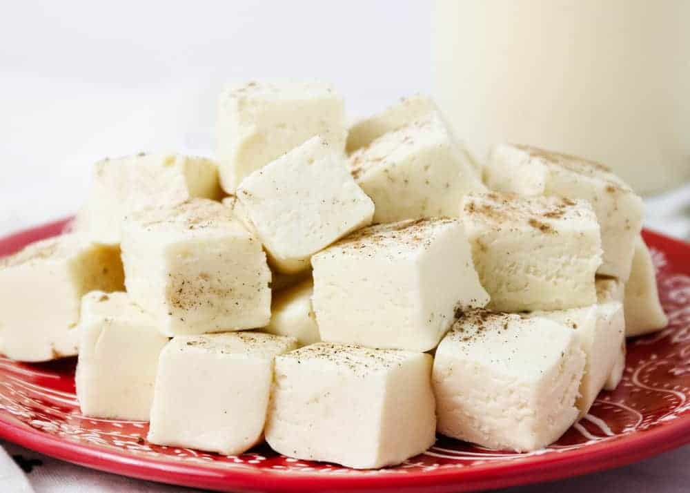 squares of eggnog fudge on a red plate