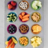 muffin tin filled with different types of snacks in each muffin cup