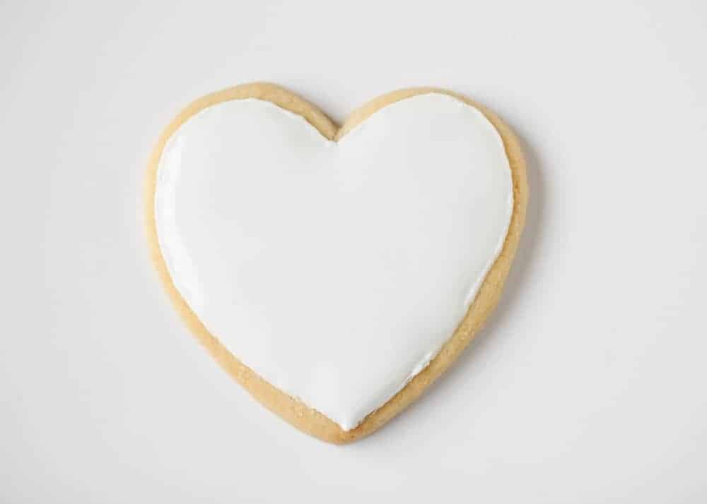 heart shaped sugar cookie topped with white royal icing