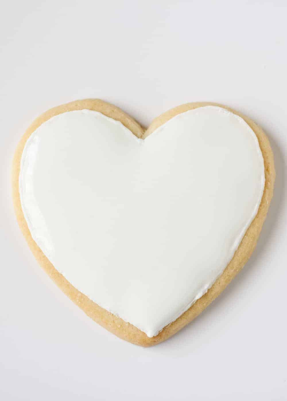 heart shaped sugar cookie decorated with white royal icing