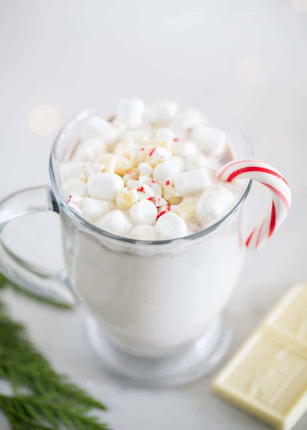 snickerdoodle hot chocolate in a glass mug with mini marshmallows and a candy cane