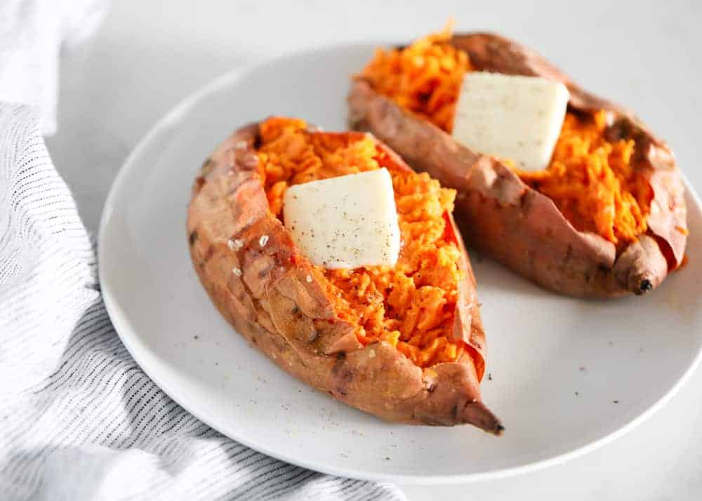 baked sweet potatoes with butter on a white plate