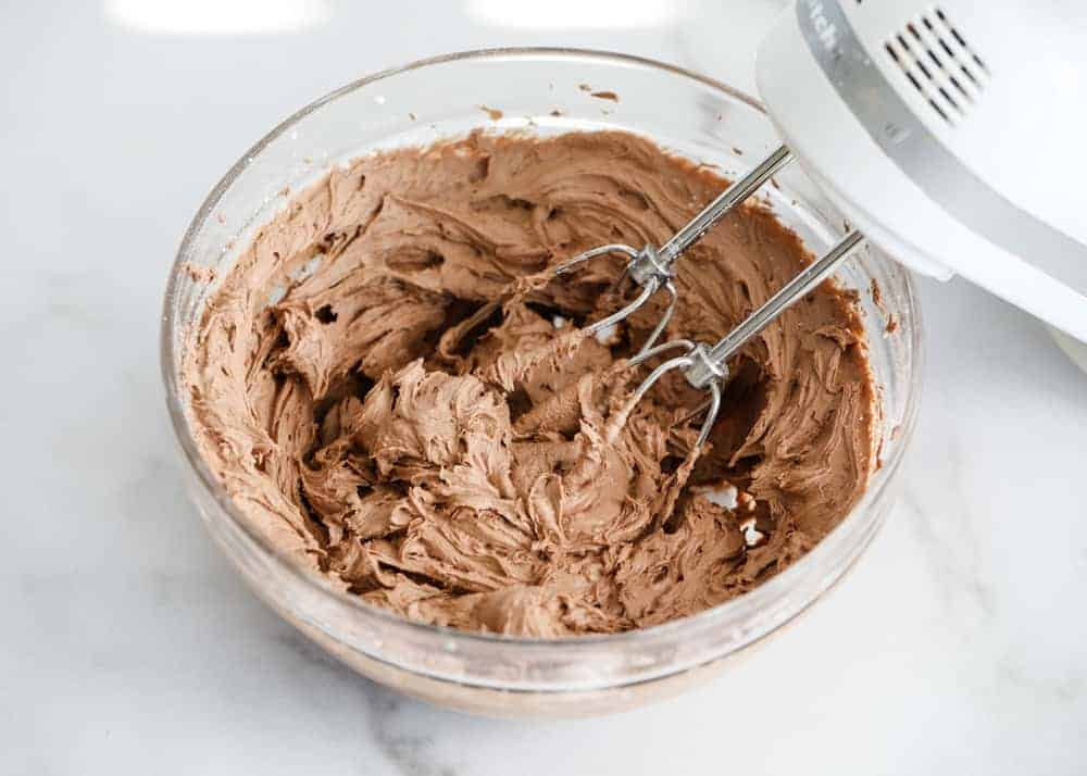 mixing chocolate buttercream frosting in glass bowl