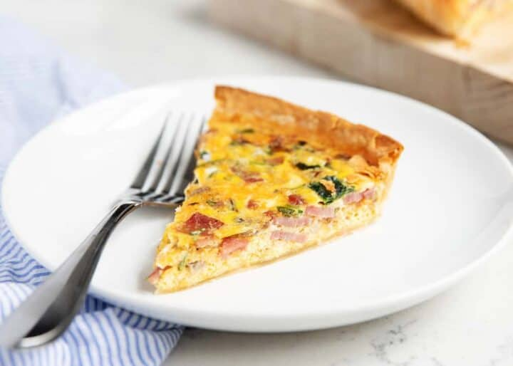 slice of ham and cheese quiche on a white plate