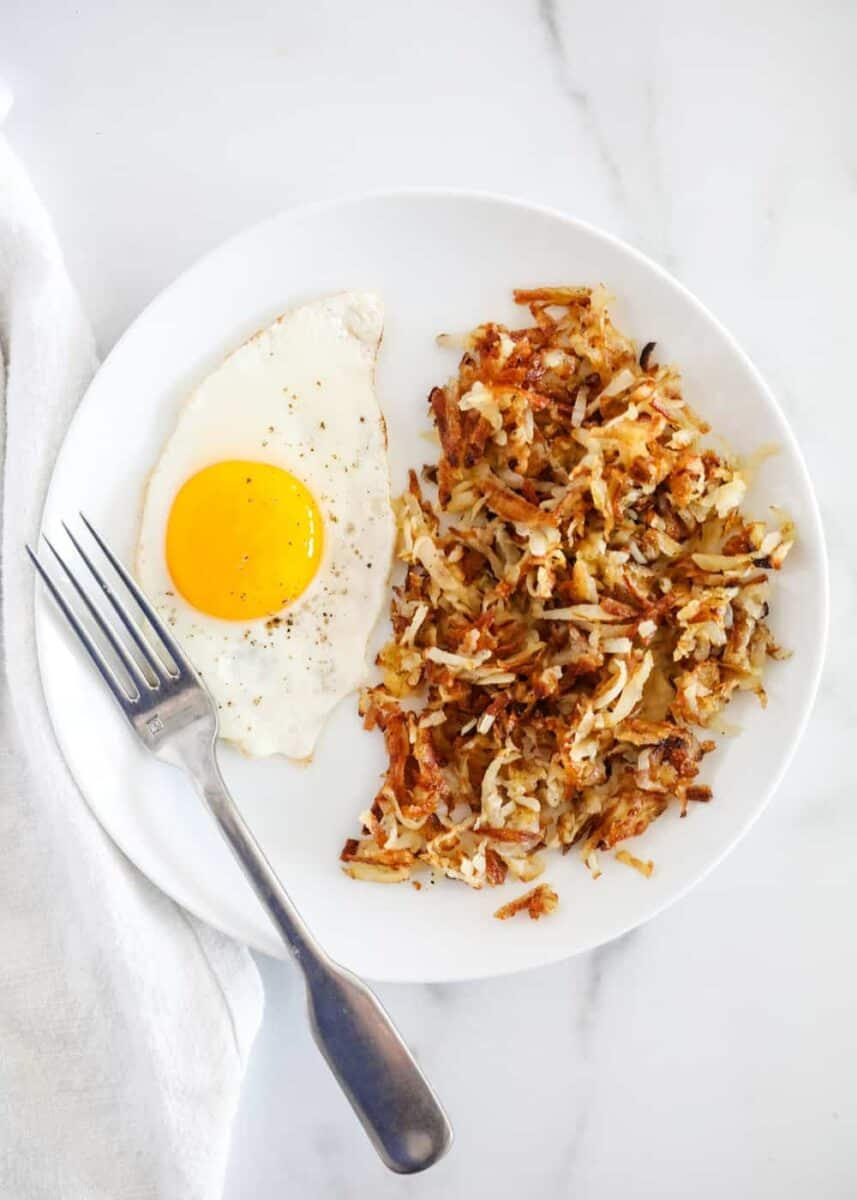 plate of hash browns with egg