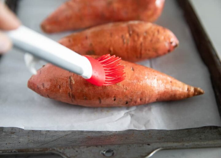 brushing olive oil on sweet potato