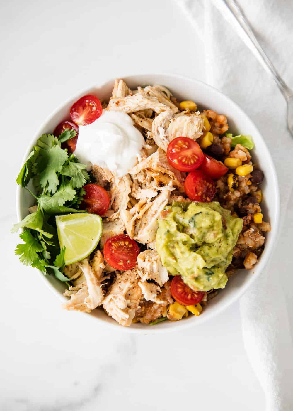 taco bowl in a white bowl with toppings loaded on