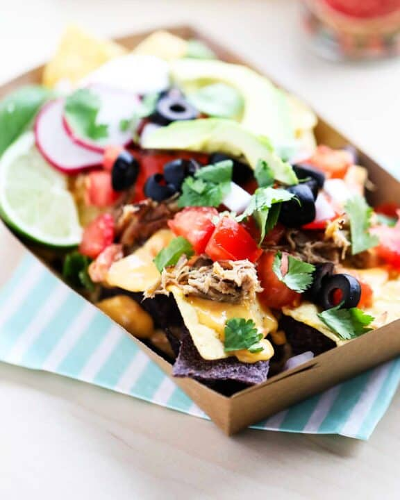 nachos with toppings in brown container