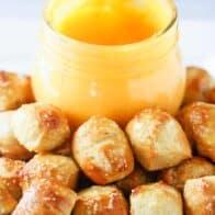 A close up of mini pretzel bites with a jar of pretzel cheese sauce