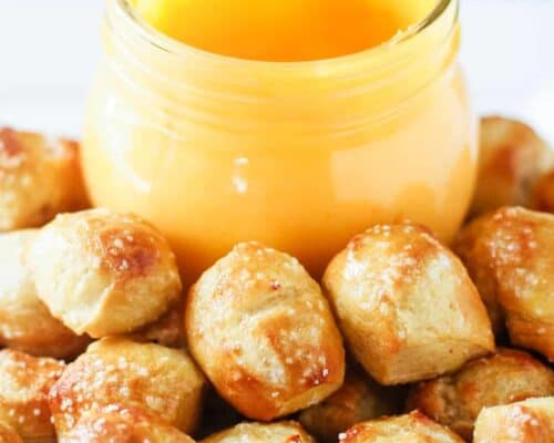 A close up of mini pretzel bites with a jar of pretzel cheese sauce