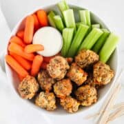 sausage balls in a white bowl with vegetables