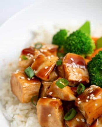 close up of teriyaki chicken in a bowl with rice and veggies