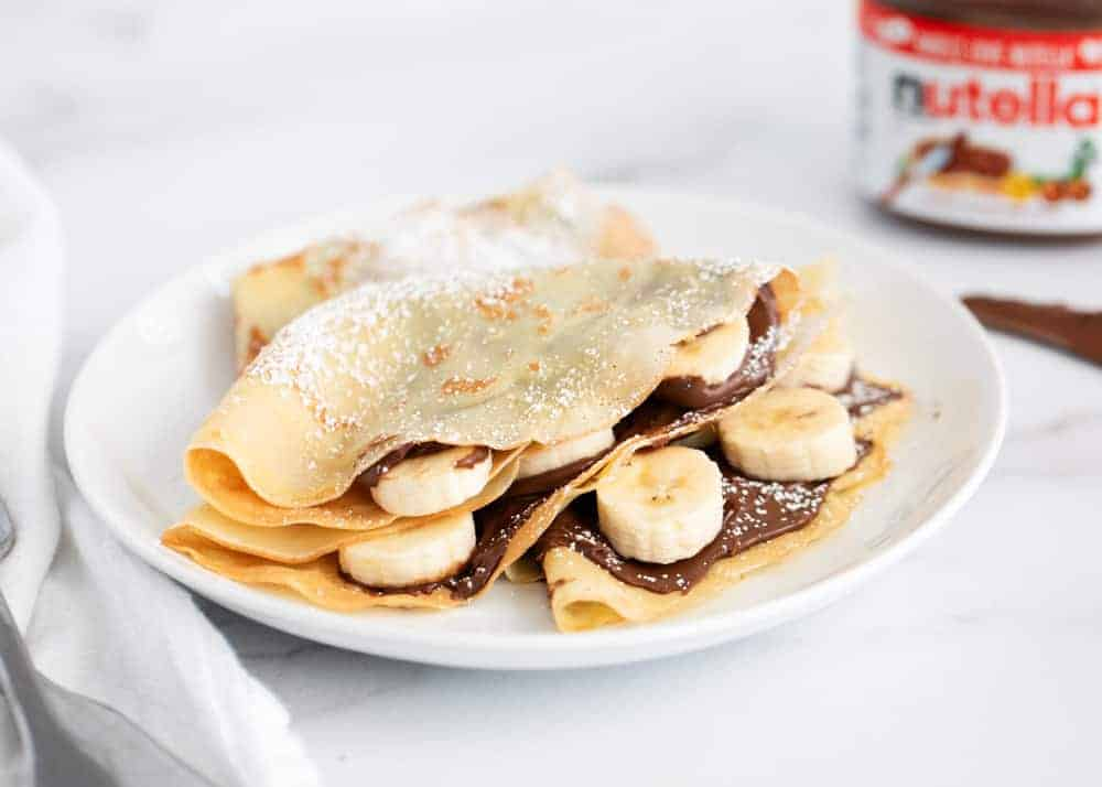 banana nutella crepes on a white plate