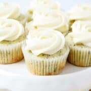 frosted lemon poppy seed cupcakes on a white cake stand