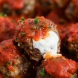 mozzarella meatballs with marinara and cheese oozing out