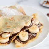 nutella crepes with bananas on white plate