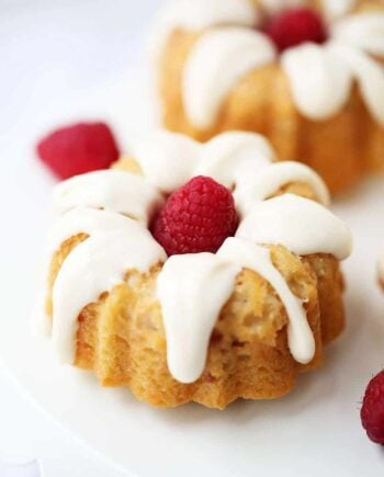 A close up of a glazed mini bundt cake with a fresh raspberry in the middle