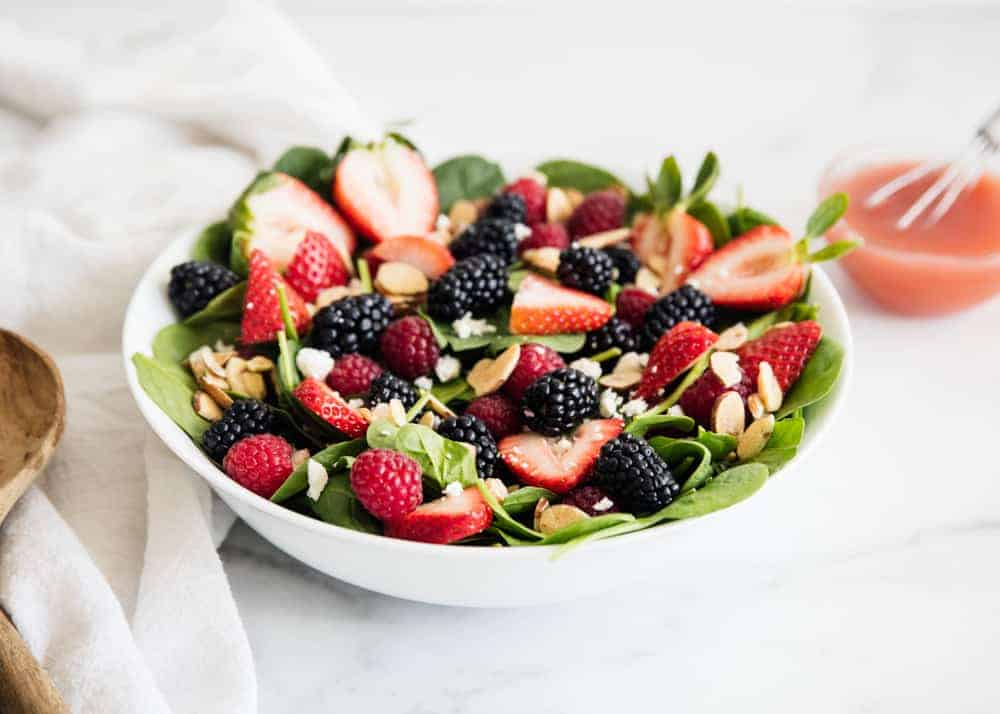 spinach berry salad in a white bowl