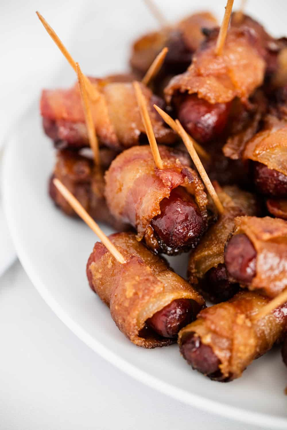 bacon wrapped smokies on white plate
