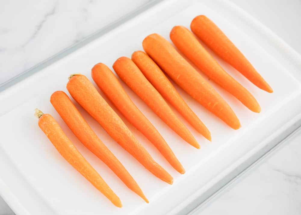 peeled whole carrots on a cutting board