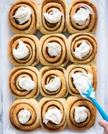 frosting cinnamon rolls with a spatula