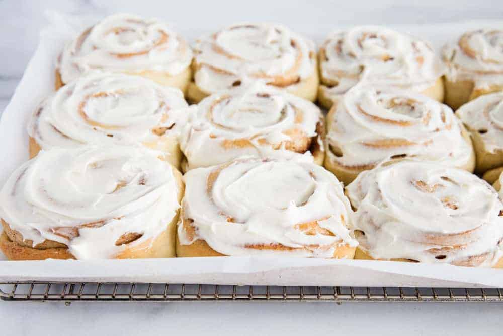 frosted cinnamon rolls on cooling rack