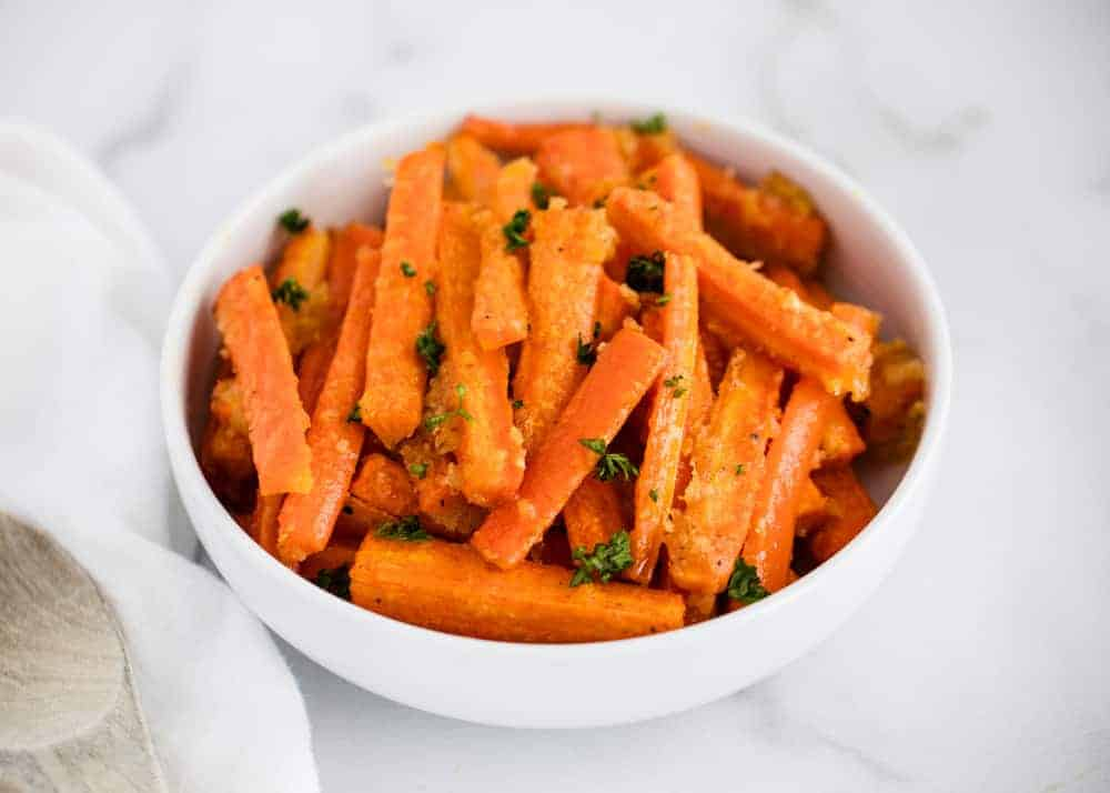 garlic roasted carrots in white bowl