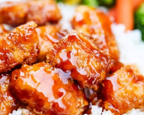 a close up of sweet and sour chicken with rice and veggies