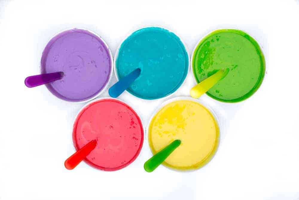 different colored batter in bowls with spoons