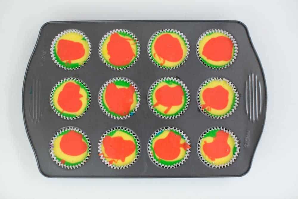 swirled rainbow cupcake batter in cupcake tin