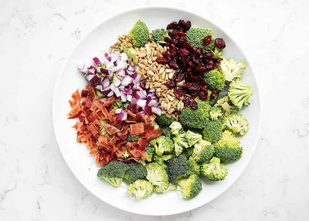 ingredients for broccoli bacon salad on white plate