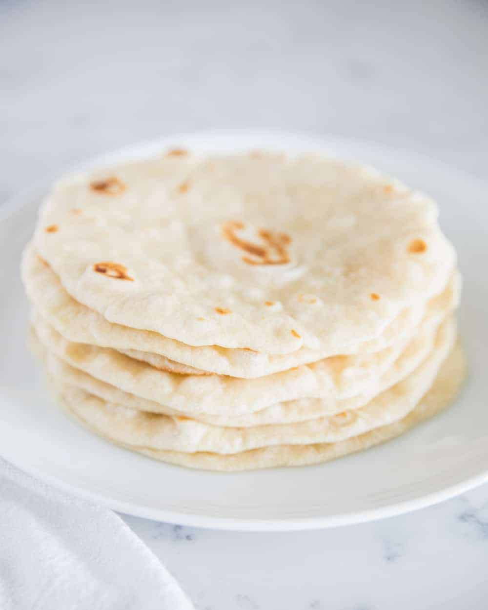 stack of homemade flour tortillas on a white plate