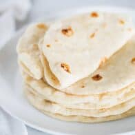 homemade flour tortillas on a white plate