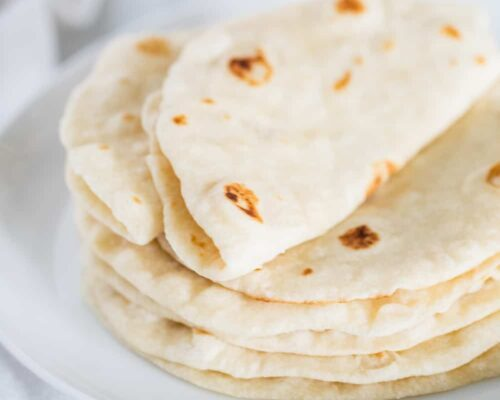 homemade flour tortillas on a white plate