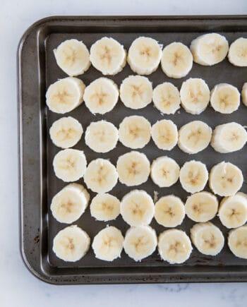 sliced bananas on baking sheet