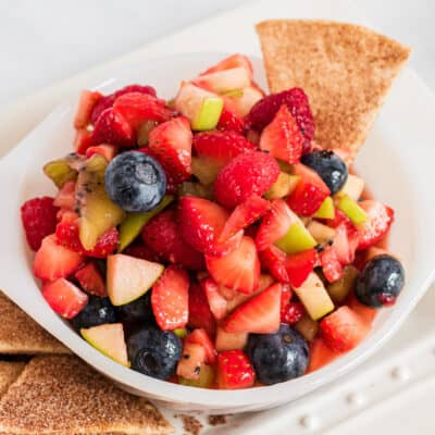 fruit salsa in white bowl with cinnamon chips