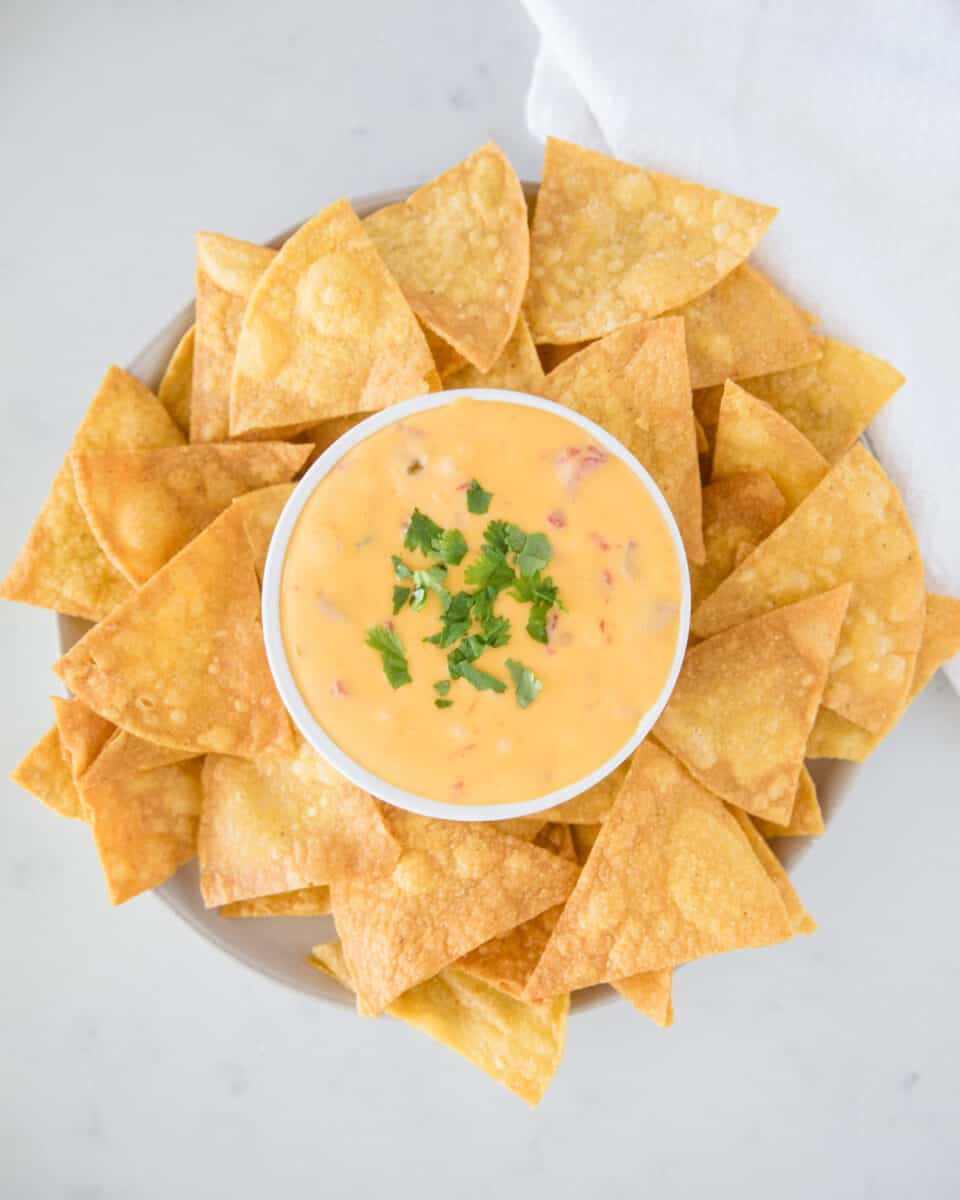 velveeta queso dip in white bowl with tortilla chips