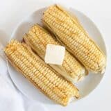 grilled corn on white plate
